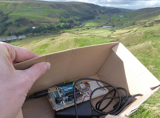 Someone holding a box with an electrical device inside, looking over hills and greenery