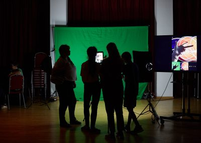 Looking onto silhouettes from the back, of four people looking into a small screen and facing a wall covering green screen. A separate screen on the right hand side with an image of a hand holding up two fingers and a thumb in front of a circular orange light.