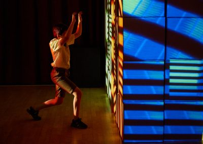 Blue and orange lights illuminating a wall, with shadows creating horizontal stripes. A man stands besides the wall posing with his knees bent and arms raised.