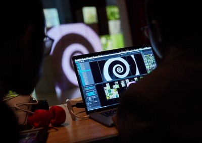 A black and white swirl in an editing software on a laptop screen. A larger swirl blurred in the background on the wall, on top of a green and black checkerboard.
