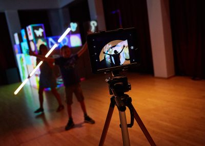 Illuminated cubes in background with silhouettes of two people, one of them is holding a long LED tube light. You can see a reflection of all of this on the camera screen in the foreground, as well as the camera set up.